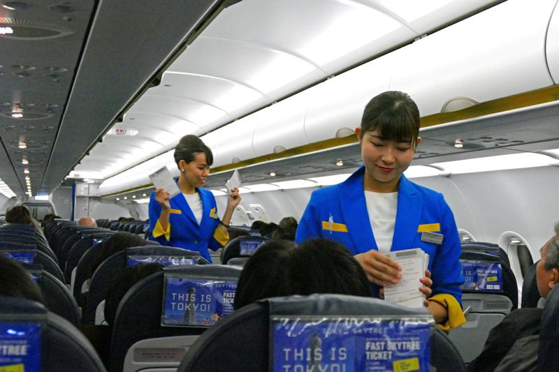 台湾で降機する人用の入国書類を配布するバニラエアの客室乗務員