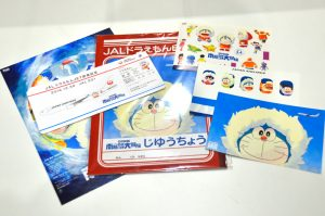 初便記念グッズとして配られたノートやポストカード、記念の搭乗券など