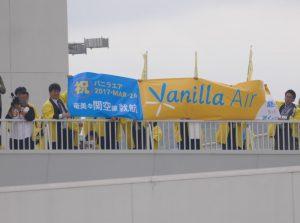 奄美空港のデッキから関西行き初便を見送るバニラエア特製の幕も掲げられた