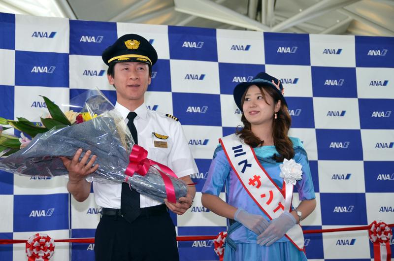 初便の秋山美弘機長に第43代ミス宮古島サンゴの根間沙弥香さんから花束が贈呈
