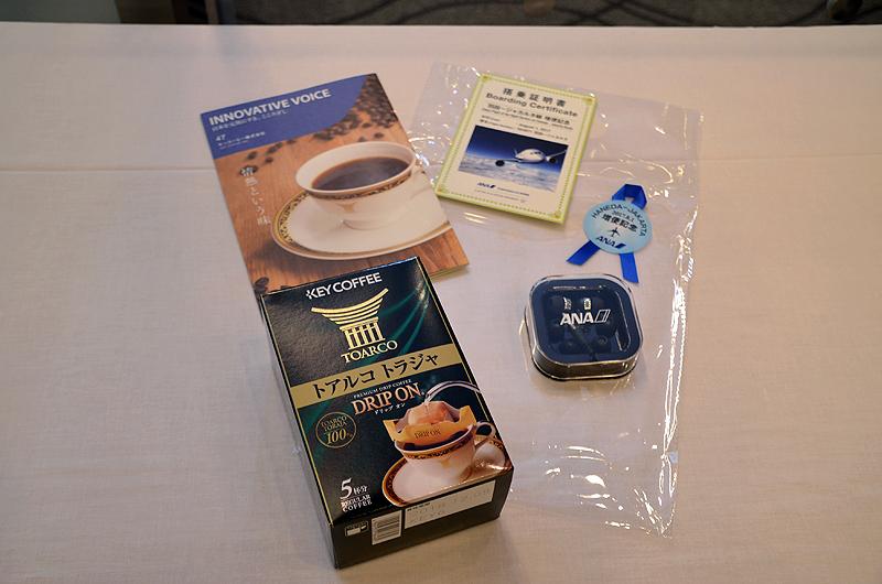 初便搭乗者にプレゼントされた、搭乗証明書、コーヒー、オリジナルイヤホンなどの記念品