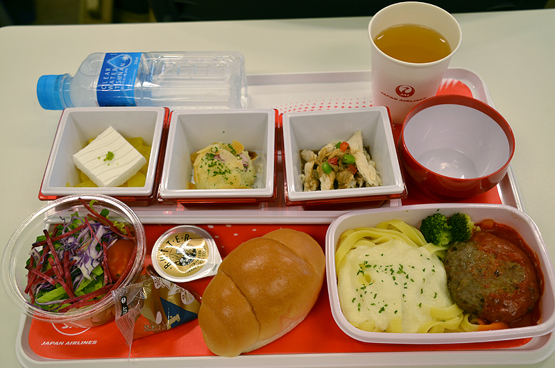 「ハンバーグ パプリカのケチャップ風ソース フェットチーネクリームソース」がメインの機内食トレイ