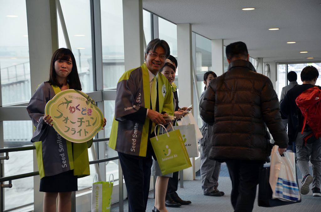 クッキーを配るソラシドエアの髙橋宏輔社長と同社のスタッフ