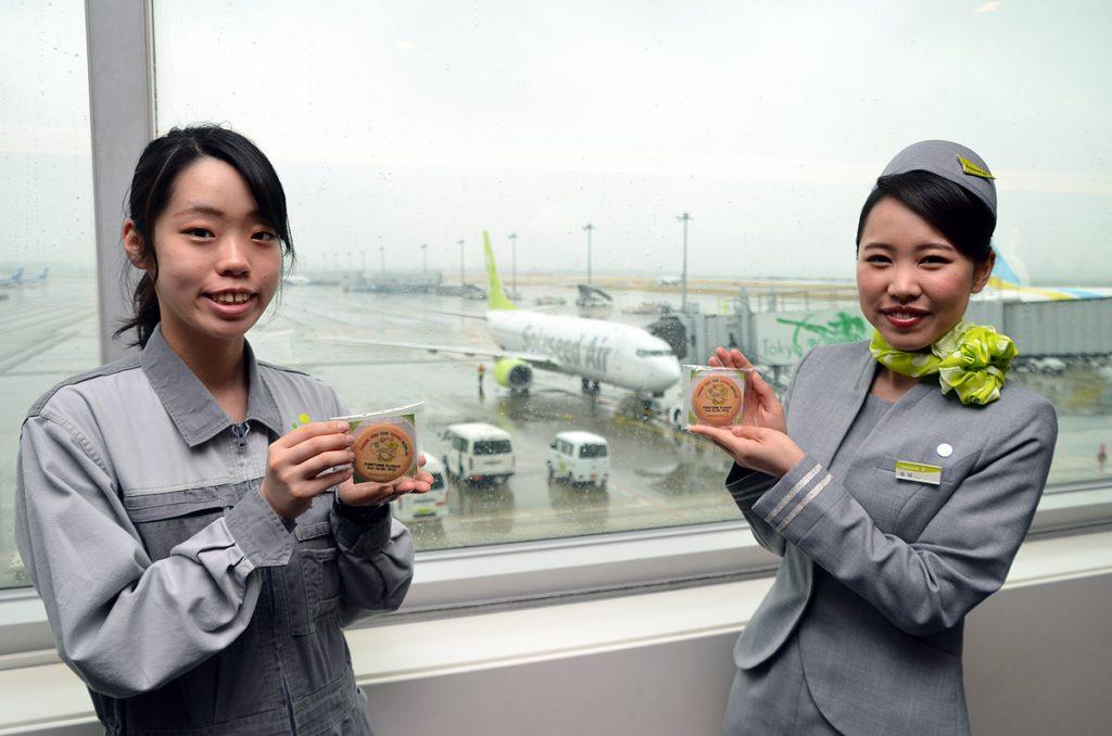 くじ付きのオリジナルクッキーを持つソラシドエアの客室乗務員と整備士