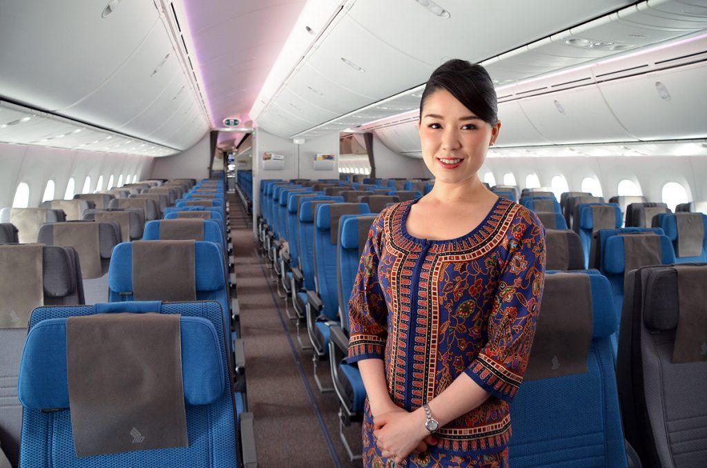 エコノミークラスをバックにしたシンガポール航空の客室乗務員