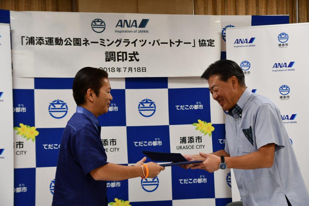 浦添市の松本哲治市長とANAの志岐隆史代表取締役副社長との間で協定書に調印した