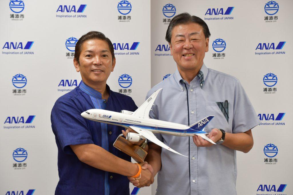ANAのモデルプレーンを持って記念撮影する浦添市の松本哲治市長とANAの志岐隆史代表取締役副社長