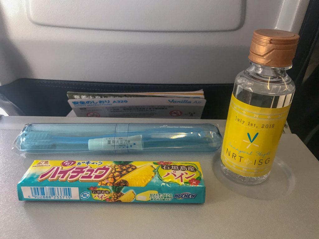 機内では沖縄の民族衣装に着替えたフライトアテンダントが記念品をプレゼントした