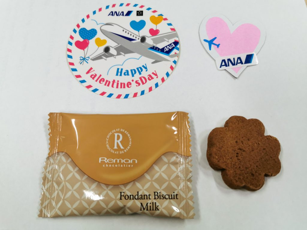 チョコレートとANAオリジナルステッカーをANAグループのグランドスタッフが羽田空港で配布する(2月13日撮影)