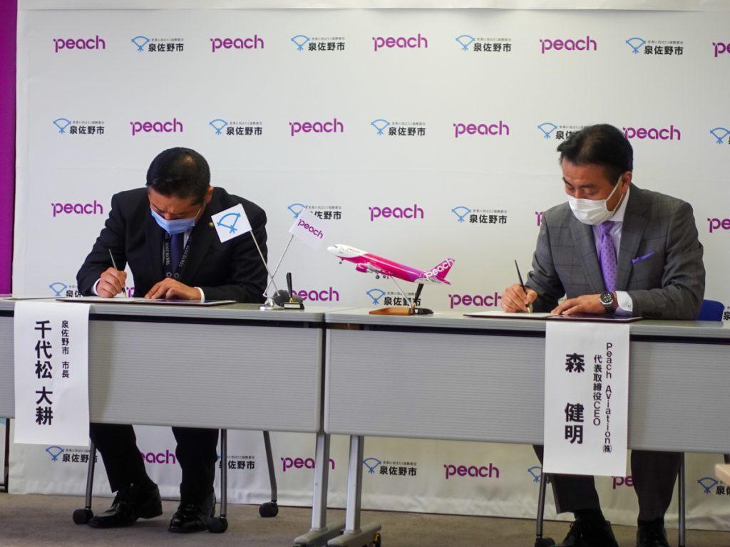 協定書にサインをする泉佐野市の千代松大耕市長とピーチの森健明代表取締役CEO